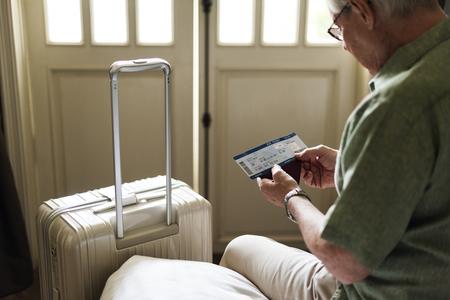 年配の男性の手の把握計画チケット荷物