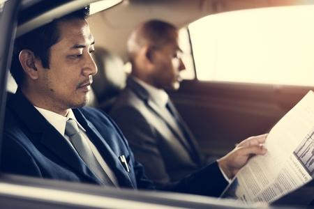ビジネスの男性が車の読む新聞の内側に座る