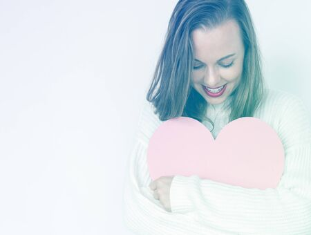 A caucasian woman is smiling holding heart. Stock Photo