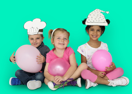 Children with paper hats and balloons