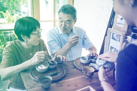 Serveerster gieten thee voor senior volwassen paar