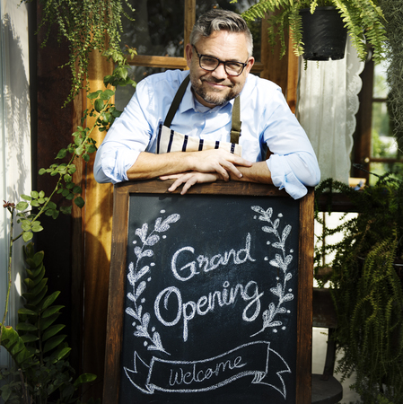 Man with grand opening blackboard in front the shop
