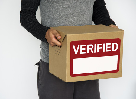 Person holding a box with verified label Reklamní fotografie