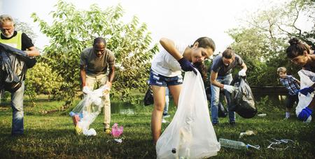 Diverso grupo de personas recogiendo basura en el parque Voluntariado de servicios comunitarios Foto de archivo - 78319097