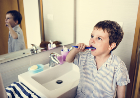 Little boy brush his teeth in restroom in the morning