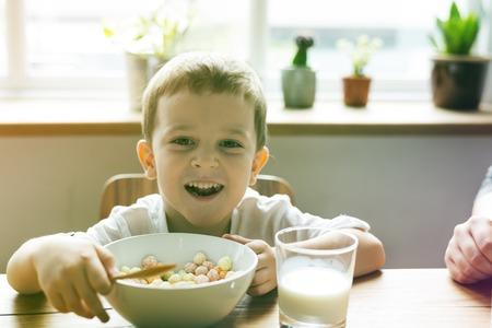Little Boy Enjoying Bowl Of Cereal Stock Photo