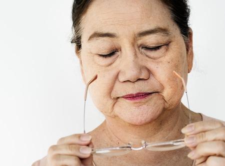 수석 성인 아시아 여자 안경을 벗고 스톡 콘텐츠