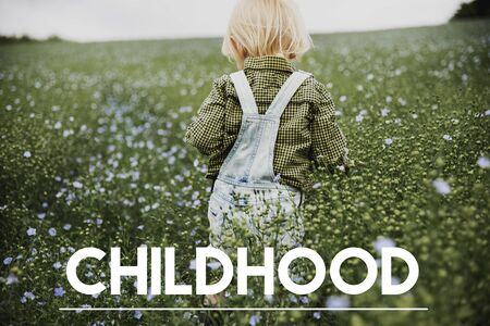 Childhood word on young boy outdoors Stok Fotoğraf