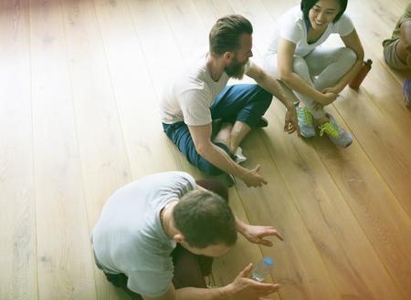 Gente sentada en un círculo en la clase de yoga