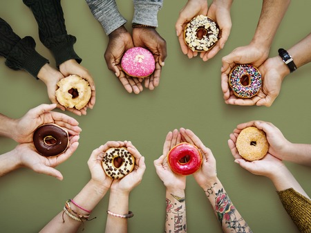 Hands holding up donuts