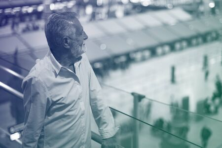 Man staring at the airport crowd downstairs Stock Photo