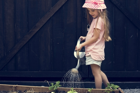 A girl is watering a plants Stok Fotoğraf