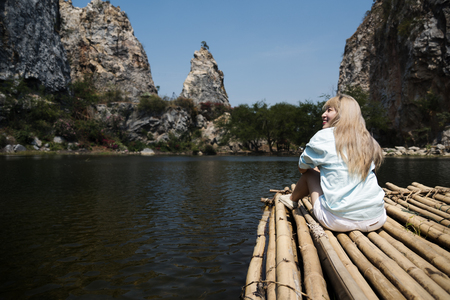 Backpack Traveler Woman is on a raft in a lake Reklamní fotografie - 78761784