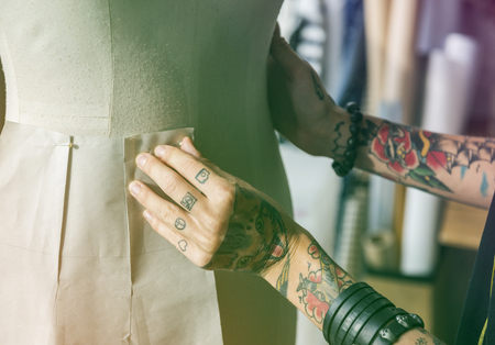 Fashion designer hands tattoo pin pattern of clothes with figure model Stock Photo