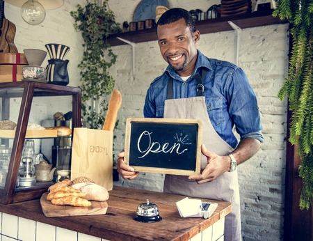African Man Holding Open Sign in Bakery Shop Stock Photo