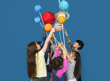 study group: Diverse group of kids holding planets on sticks isolated background Stock Photo