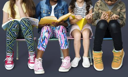 Diverse group of kids sitting in a row reading books 版權商用圖片