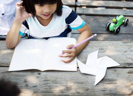 ノートのほとんどのアジアの少年図面 写真素材