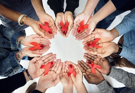 Group of hands holding red ribbon stop drugs and HIVAIDS awareness