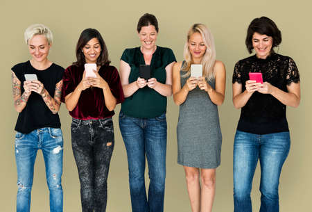 woman on phone: Happiness group of girlfriends smiling and conneted by mobile phone Stock Photo