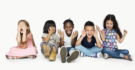 一緒に遊ぶ子供たちの多様なグループの顔を覆うと 写真素材