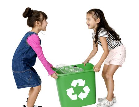 niños reciclando: Niños y botellas de plástico en una papelera de reciclaje