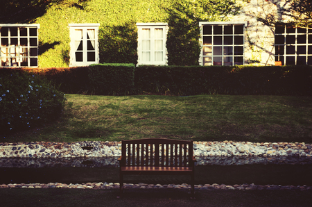 緑の草の庭の前でリラックスするためのベンチ