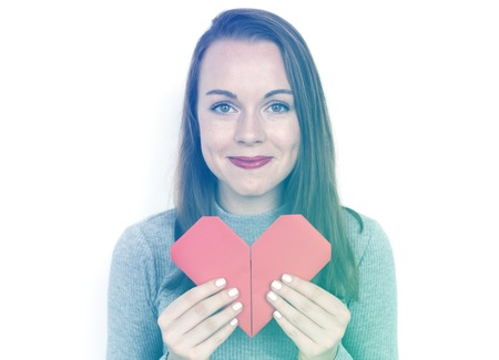 A caucasian woman is holding origami heart shape. Stock Photo