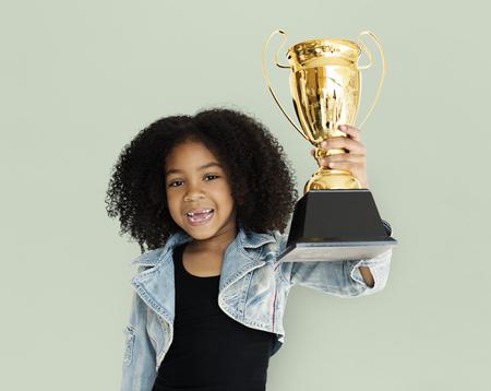 幸せの小さな女の子持株トロフィー 写真素材