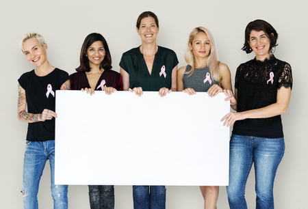 Group of women with pink ribbon and holding blank banner for breast cancer awareness Stock Photo - 78891817
