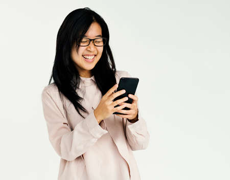 woman on phone: Asian girl smiling browsing phone studio portrait Stock Photo