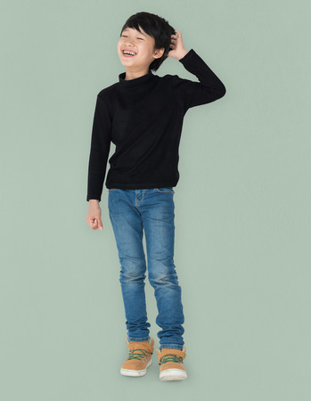 Asian kid laughing scratching his head portrait Stock Photo
