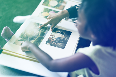 African girl looking at the photo album Reklamní fotografie