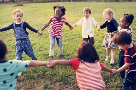 Gruppe von verschiedenen Kindern, die auf dem Feld zusammen spielen Standard-Bild - 79318470