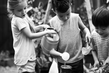 Children are in the garden watering the plants Reklamní fotografie
