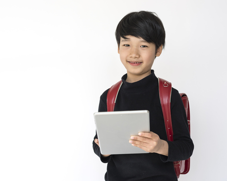 Little cute and adorable student boy using digital tablet is back to school