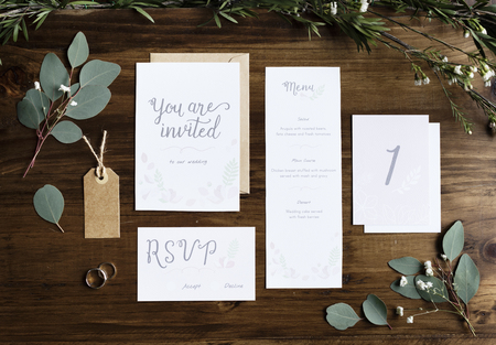 Wedding Invitation Cards Papers Laying on Table Decorate With Leaves Stock Photo