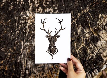 Human hand holding wild life moose perforated paper craft in nature