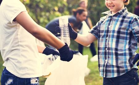 Little Boys Picking Up Plastic Bottle in The Park Volunteer Community Service