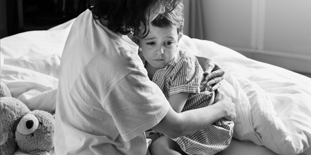 Moeder knuffel en troost de kleine jongen van nachtmerrie