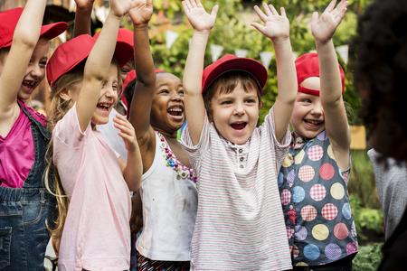 Gruppe verschiedene Kinderhände, die freundlich zusammen oben anheben Standard-Bild