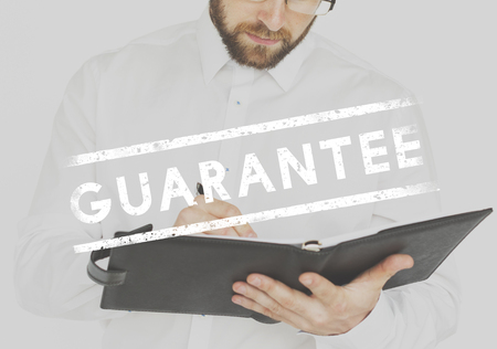 Businessman working and writing with guarantee stamp