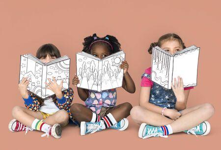 Little Children Reading Sitting Down Stock Photo