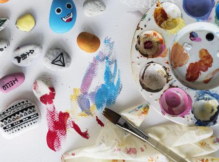 Schilderpalet Pebbles Brushes White Table Stockfoto - 79589930