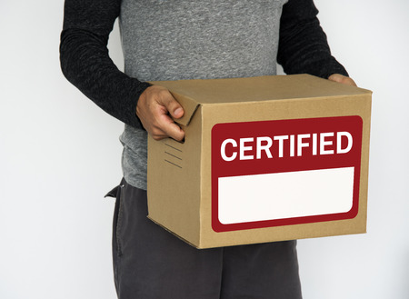 Person holding a box with certified label Reklamní fotografie