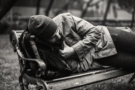 Bezdomny dorosły człowiek śpi na ławce w parku