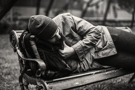Homeless Adult Man Sleeping on Bench in The Park Stok Fotoğraf - 79643620
