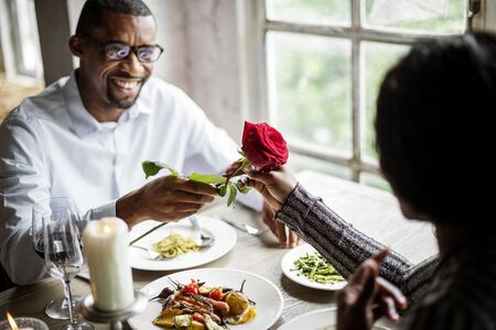Romantic Man Giving a Rose to Woman on a Date Reklamní fotografie