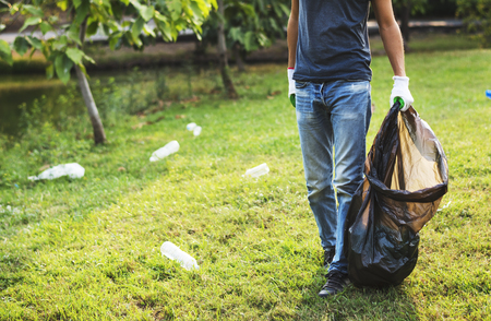 Man with Plastic Bag Pick Up Bottles in The Park