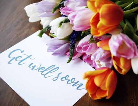 Bouquet de fleurs de tulipes avec carte de souhaits de bien se remettre Banque d'images